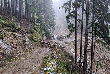Back to mud flow above third switchback. The rocky waterfall ledge is what remains of the old pretty waterfall by the road here. Map: location 5
