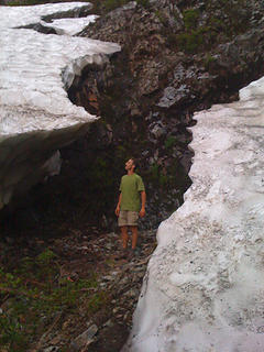 Me between remnants of a massive snow bank at a gully crossing around 3750 ft