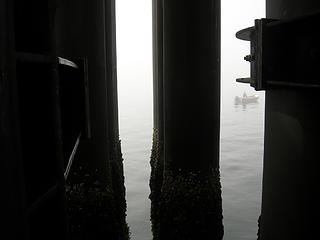Lone fisherman between the pillars at beginning of Kingston ferry ride