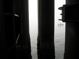 Lone fisherman between the pillars at beginning of Kingston ferry ride