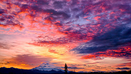 Sunrise over Bonney Lake, Washington with Mount Rainier casting a shadow against the clouds.