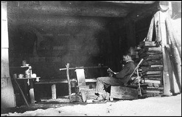 Man reading by the fire on a snowy day at the Pelton Creek Shelter on the Queets River. NPS image. Courtesy Henry Bonham. (BON.001.019)