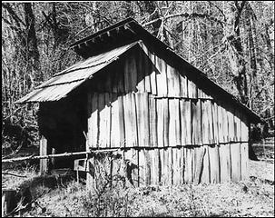 Front corner elevation of Bob Creek Shelter. A can and an identifying sign hang in front of shelter. NPS photo, courtesy of Russ Dalton (RDA.002.023)