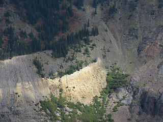 Looking across the valley of Glacier Creek, a sizeable patch of lighter-colored material stands out,  referred to as the Chromatic Moraine.  It looks like it is sun-lit, but not so much. The yellow band is hydrothermally-altered, sulphur-rich tephra, called YP tephra. It erupted from Sherman Crater, not the summit crater of Baker, in 1843. How did it get to this opposite side of Mount Baker? Kevin Scott and USGS colleagues believe it was blasted out of Sherman Crater as a damp mass during phreatic, or steam-rich, eruption(s), blew over the summit of Baker, and plopped down on the glacier surface. It was carried down the glacier in conveyor-belt fashion and eventually plastered against the moraine. Note that it is not a layer [i:ad231954ba]within[/i:ad231954ba] but is inset [i:ad231954ba]against[/i:ad231954ba] the moraine. The deposit is nowhere as thick as it appears. The apparent thickness is because the distinctively colored ash washes down the moraine walls as  a thin veneer.