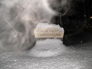 Trailhead sign, with steaming breath lit up by the flash