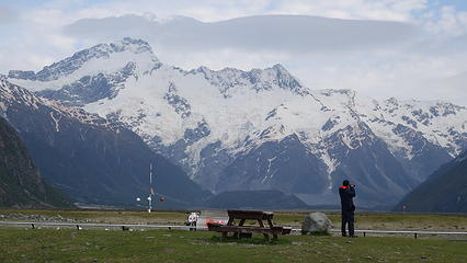 A tourist enjoys the view of Mount Sefton from the airport