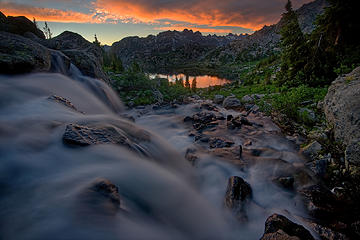 A creek filled by snowmelt cascades toward Island Lake in the Wind River Range as the sun sets.