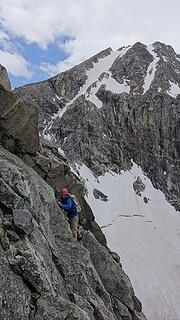 Eric traversing back around the low cliff on slabs with the crux step just behind him