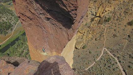 Hikers can be seen on the approach trail as the second, safely belayed from above, prepares to launch...